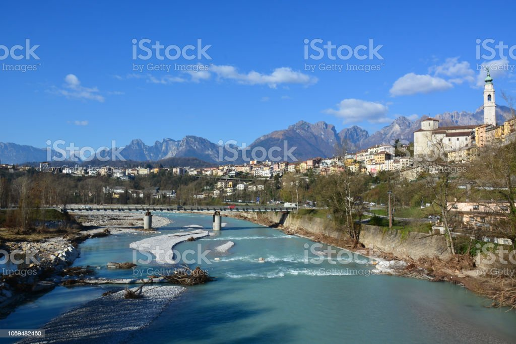the Piave river, sacred to the homeland, flows slowly through the city of Belluno in Italy - foto stock