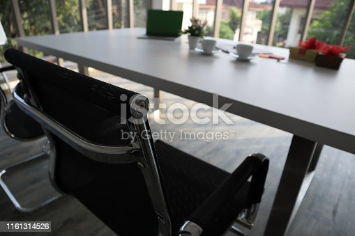 1064053478 istock photo The picture of office with two black chairs and white table. Cups and laptop place on the table with others.  As an office for recruiting and interview the new applicants 1161314526