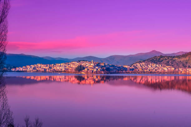 The picturesque city of Kastoria reflected on the lake of Orestiada at sunset. stock photo