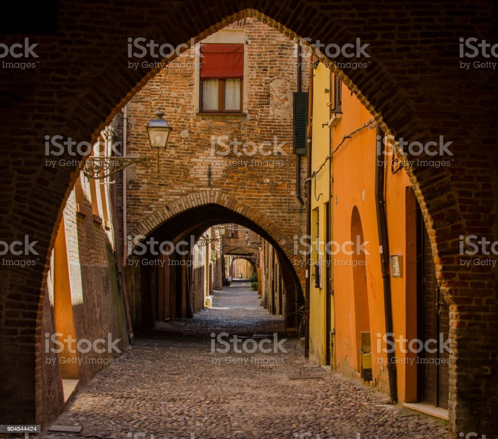 The picturesque  medieval street of Ferrara with arches stock photo