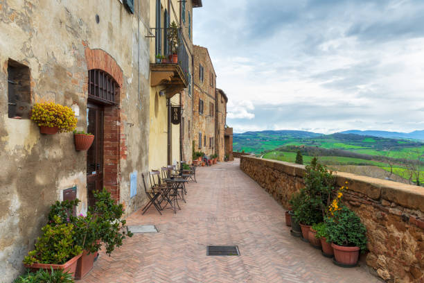The picturesque narrow streets of Pienza, Italy A narrow picturesque medieval street along the city wall and view to the valley in old town of Pienza in Tuscany, Italy pienza stock pictures, royalty-free photos & images