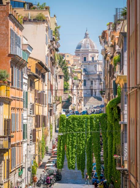 the picturesque rione monti in rome, with the basilica of santa maria maggiore in the background. - rome road central view foto e immagini stock