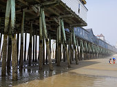 Underside of the Pier at Old Oarchard Beach, Maine. The wooden poles are barnacle encrusted, A carnival can be seen in the background, mostly hidden in the morning fog.