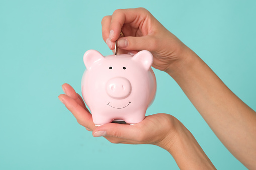 Femle hand isolated on pink background putting coins to the piggy bank.