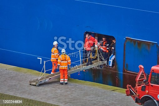 Bremerhaven, Germany, January 16., 2020: The pilot leaves the huge cargo ship through an opening on the side and a beam on the edge of the lock