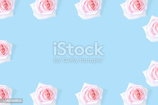 1147995495 istock photo The pink rose pattern is framed against a blue background. 1168399805