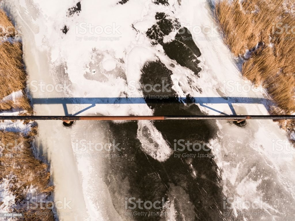 The pipe of the factory above frozen river. stock photo
