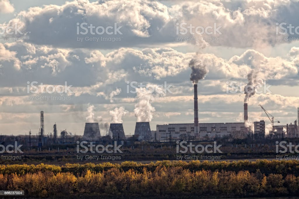 the pipes of a large plant smoke in the sky stock photo
