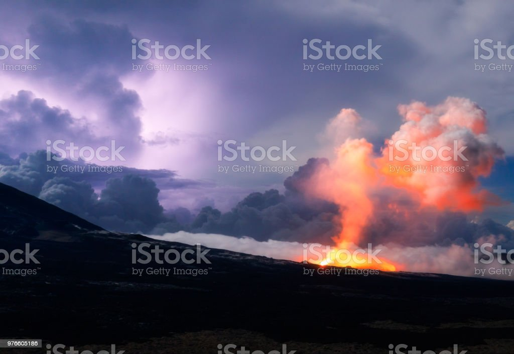 The Piton de la Fournaise volcano during a thunderstorm in Reunion...