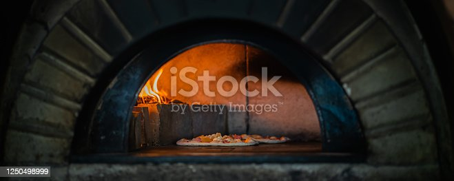 The pizza is baking in the pizza oven