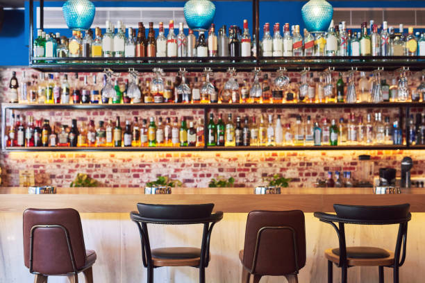 The place to go to have fun Shot of an immaculate bar with many bottles and glasses with no people stool stock pictures, royalty-free photos & images