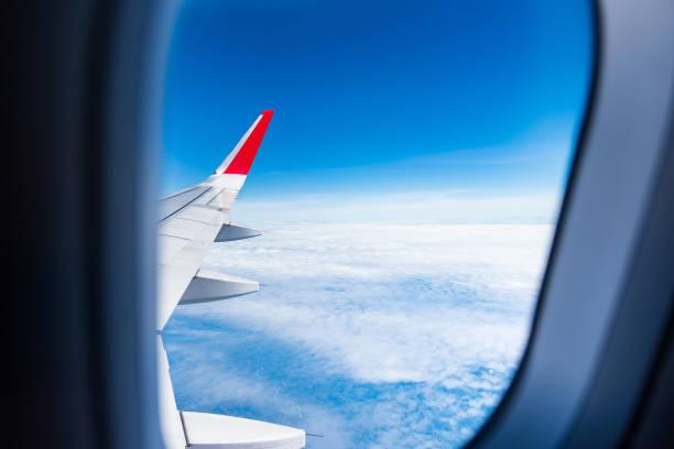 Das Flugzeug bockt Wolken mit blauem Himmel, die sich durch das Fenster des Flugzeugs fotografieren lassen. Thailand. – Foto