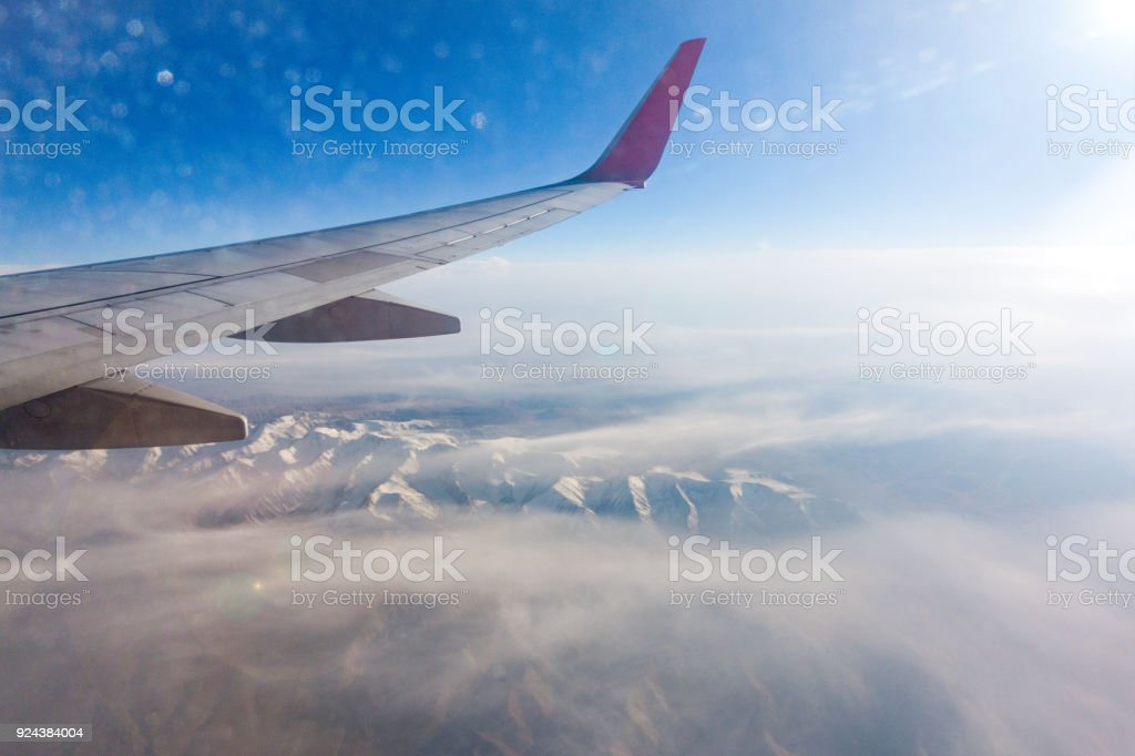 The plane flew over snow-capped mountains stock photo