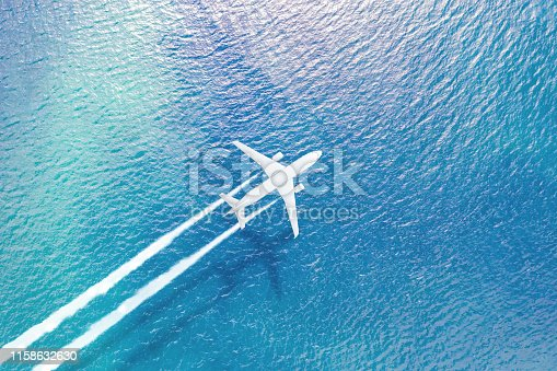 1058205304 istock photo The plane flying over the sea leaves a white trail of smoke, a shadow on the surface of the water. 1158632630