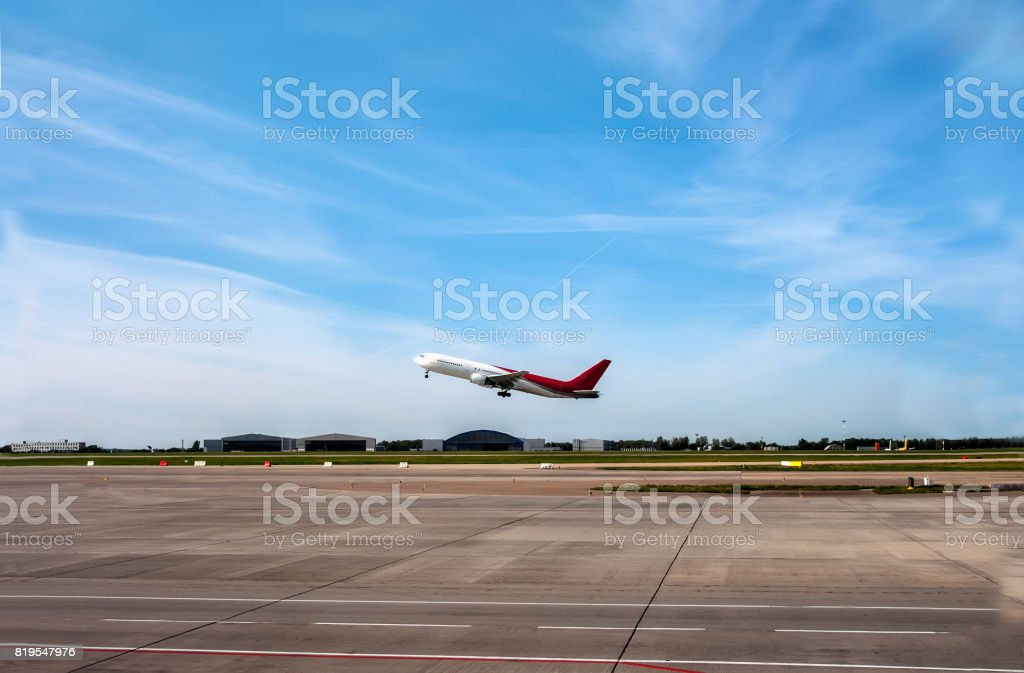 The plane going to take off on the runway on the background of blue sky with Cirrus clouds. stock photo