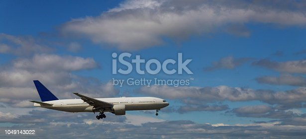 864534880 istock photo The plane in the sky goes to the landing against a white fluffy clouds. 1049143022