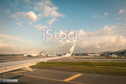 902818356 istock photo The plane is about to run the runway at Kuala Lumpur Airport. At sunset 1210004908