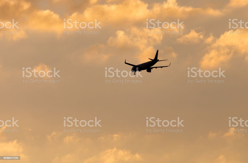 The plane is landing at sunset stock photo