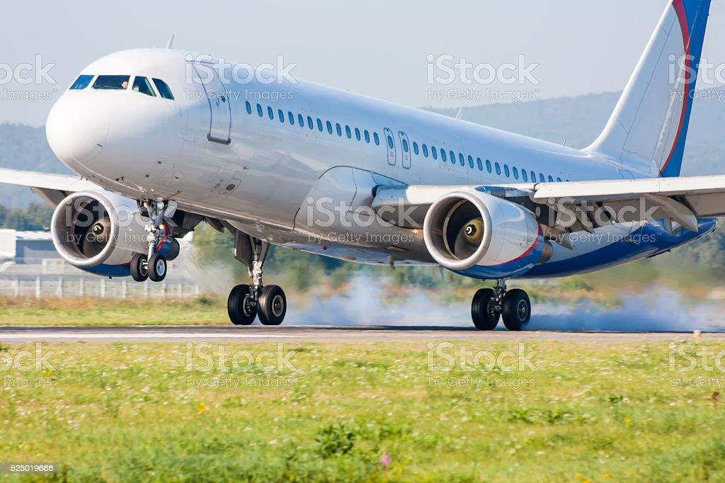 Самолет приземляется. Касаясь взлетно-посадочная полоса с дым стоковое фото