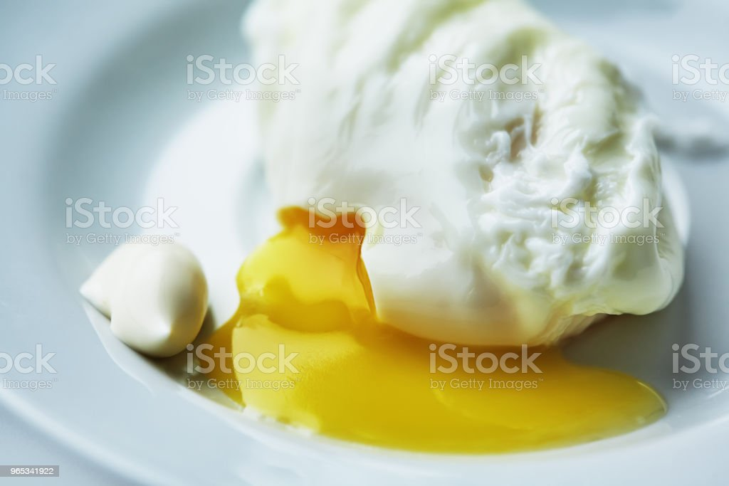 The poached egg is on a white plate royalty-free stock photo