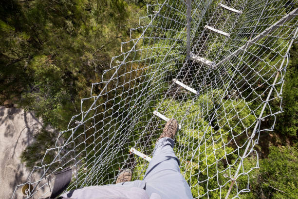 The point of view of a hiking man in grey pants crossing a suspension bridge over river rocks stock photo