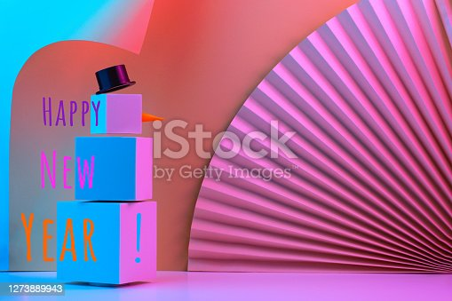 The polygonal snowman of cubes is illuminated with neon light, against the background of the fan and corners of the paper. Trend Concept 2020, 2021