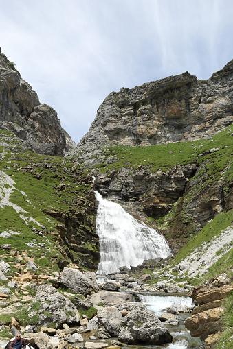 The Ponytail Waterfall (Cascada de la Cola de Caballo) as the Arazas river flows into the high rocky mountains and green pastures in the Ordesa valley (Valle de Ordesa) national park, in Aragon, Spain