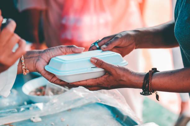 Den Armen in der Gesellschaft wird geholfen durch Mittagessen, Vom Teilen mitfühlender Menschen: Konzepte von Lebensmittelspenden und Hilfe – Foto