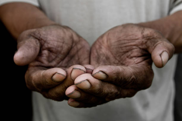 The poor old man's hands beg you for help. The concept of hunger or poverty. Selective focus. Poverty in retirement. Alms stock photo