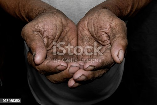 883034410 istock photo The poor old man's hands beg you for help. The concept of hunger or poverty. Selective focus. Poverty in retirement. Alms 973465350