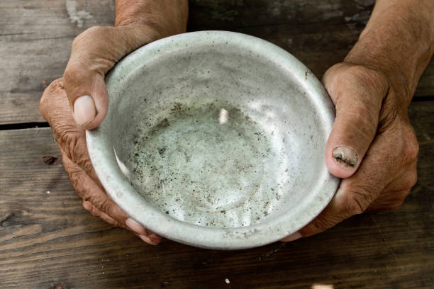 The poor old man's hands hold an empty bowl of beg you for help. The concept of hunger or poverty. Selective focus. Poverty in retirement. Alms stock photo