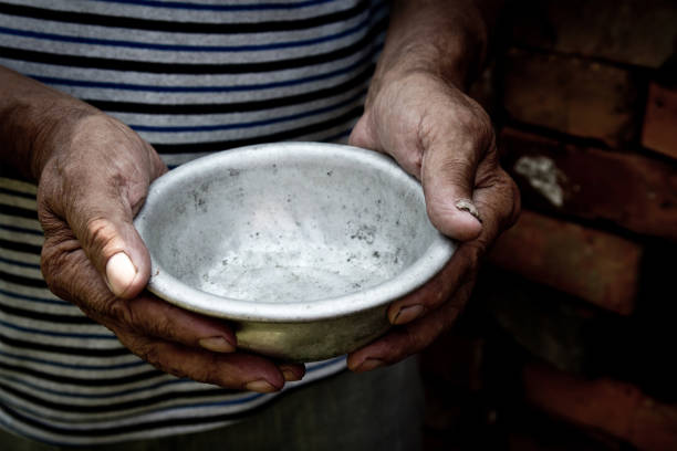 The poor old man's hands hold an empty bowl. The concept of hunger or poverty. Selective focus. Poverty in retirement. Homeless. Alms stock photo