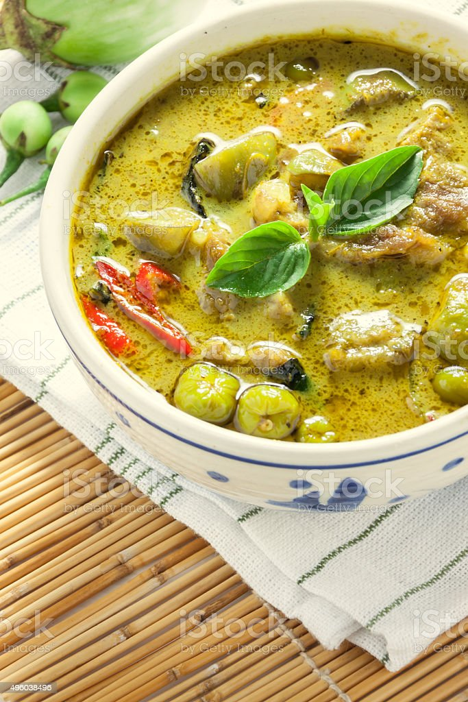 the pork green curry and eggplant on bamboo background stock photo