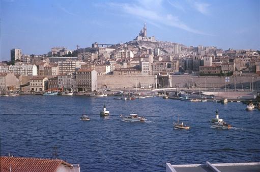 Marseille, Provence-Alpes-Côte d'Azur, France, 1969. The port of Marseille. In the background, Notre-Dame de la Garde.