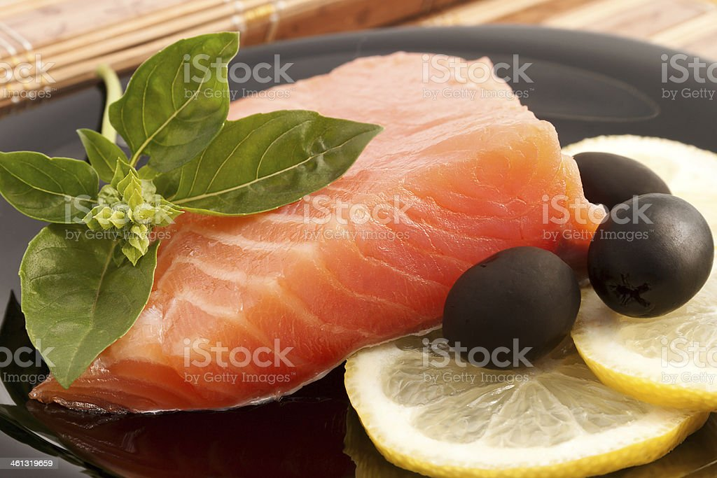 The portion of delicious salmon with basil, lemon and olives stock photo