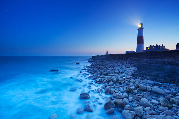 The Portland Bill Lighthouse in Dorset, England at night The Portland Bill Lighthouse on the Isle of Portland in Dorset, England at night. beacon stock pictures, royalty-free photos & images