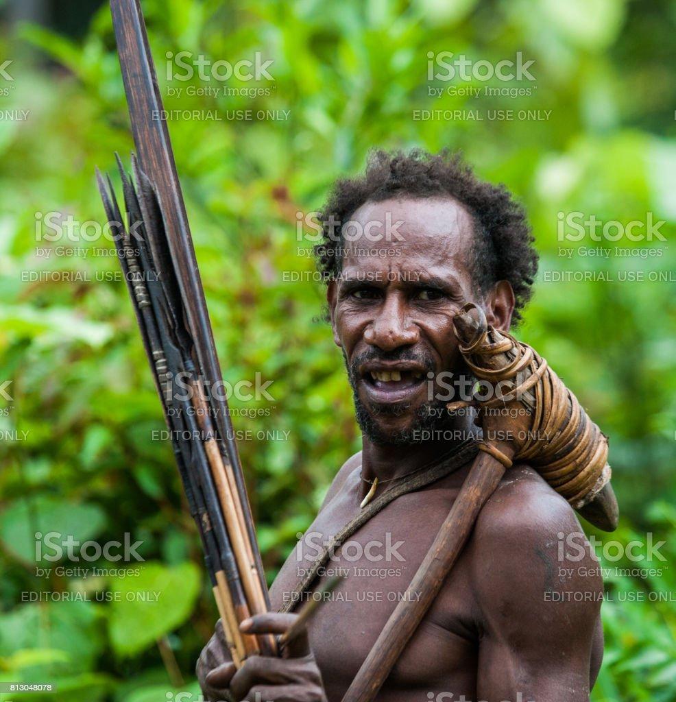 The Portrait Korowai man hunter with arrow and bow. Tribe of Korowai (Kombai , Kolufo). stock photo