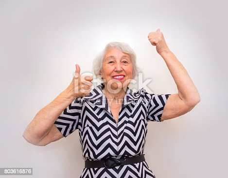 istock The portrait of a cheerful senior woman gesturing victory over pink 803616876
