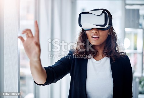 Shot of a young businesswoman wearing a VR headset in an office