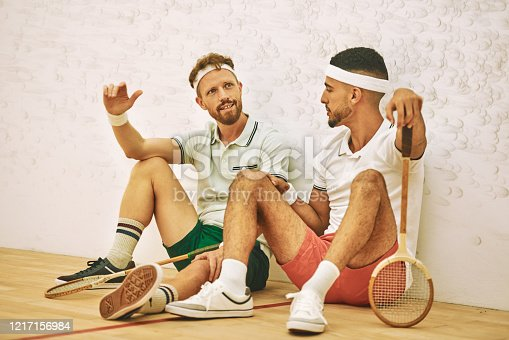Shot of two young men chatting after playing a game of squash