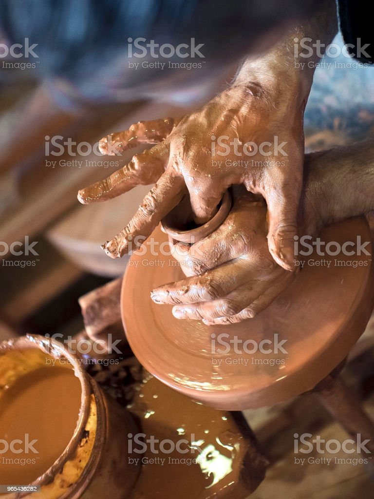 The potter's hands are shaped a cup from a clay. The process of creating pottery on a potter's wheel. The master ceramist works in his studio. Close-up, only hands. Crockery from clay own hands zbiór zdjęć royalty-free