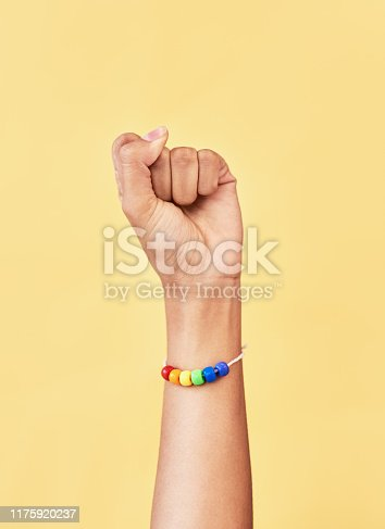 Studio shot of an unrecognizable woman raising a fist while wearing a rainbow bracelet