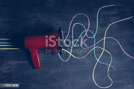 Red megaphone on a blackboard. There are multicoloured lines drawn on the chalkboard, going out of the megaphone drawn on the blackboard.