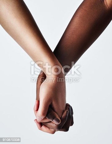Cropped studio shot of two women holding hands