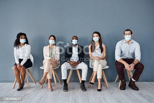 Portrait of a group of businesspeople wearing face masks while sitting in line against a grey background