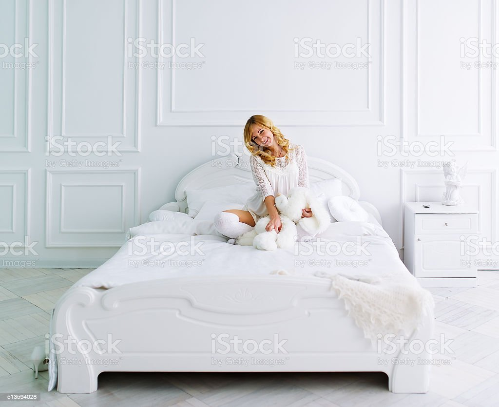 The pregnant woman sits on a bed in white bedroom stock photo