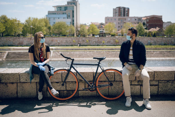 The prescribed measure of social distance is one bicycle Young couple trying to maintain their relationship during a pandemic. They enjoy their love, applying all protection measures and wearing protective masks and gloves. romantic activity stock pictures, royalty-free photos & images