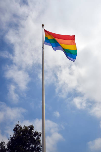 the Pride Flag on a tall pole against a blue skies and puffy white clouds stock photo