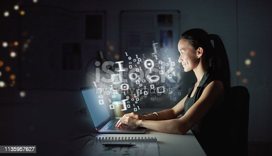 Shot of a young businesswoman using a computer with cgi graphics coming out of the screen at night