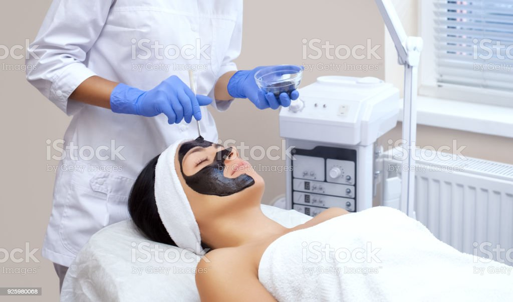 The procedure for applying a black mask to the face of a beautiful woman. stock photo